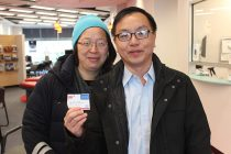 Paul Lee and Mimi Man at the Garden City, N.Y., branch, holding a membership card.